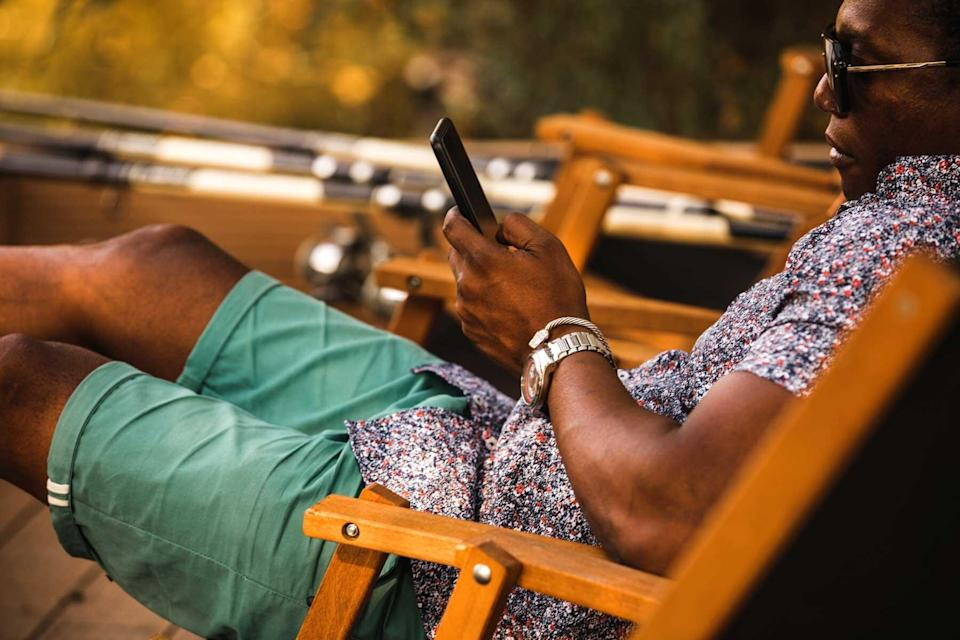 Side view of young man relaxing in a chair, fishing and scrolling through his smart phone to pass time.