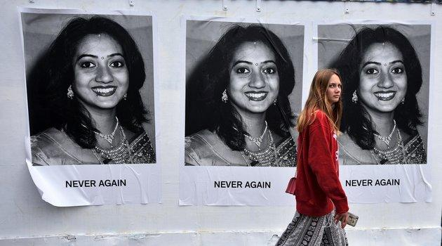 A young woman walks past art work featuring Savita Halappanavar