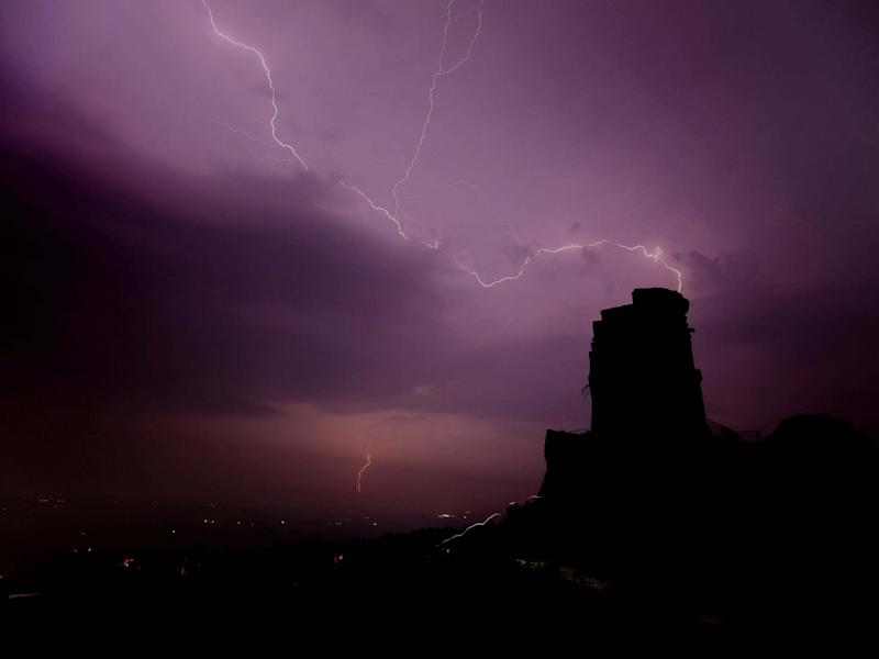 Lightning is seen over Mow Cop, Staffordshire: REUTERS
