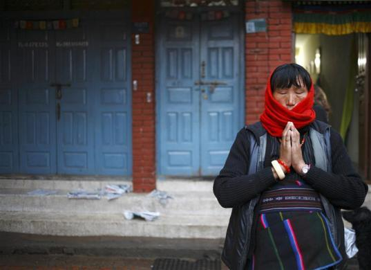 A Tibetan woman offers prayers in front of the Boudhanath Stupa in Kathmandu, February 8, 2012.