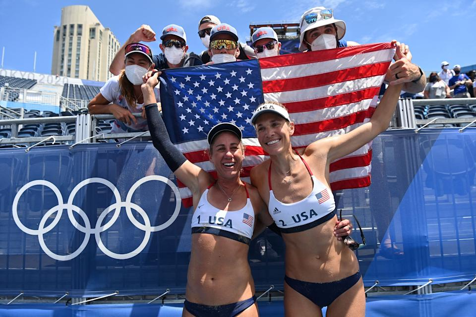 <p>USA's April Ross (L) and Alix Klineman celebrate with the USA flag after winning their women's beach volleyball final match between Australia and the USA during the Tokyo 2020 Olympic Games at Shiokaze Park in Tokyo on August 6, 2021. (Photo by Angela WEISS / AFP)</p>