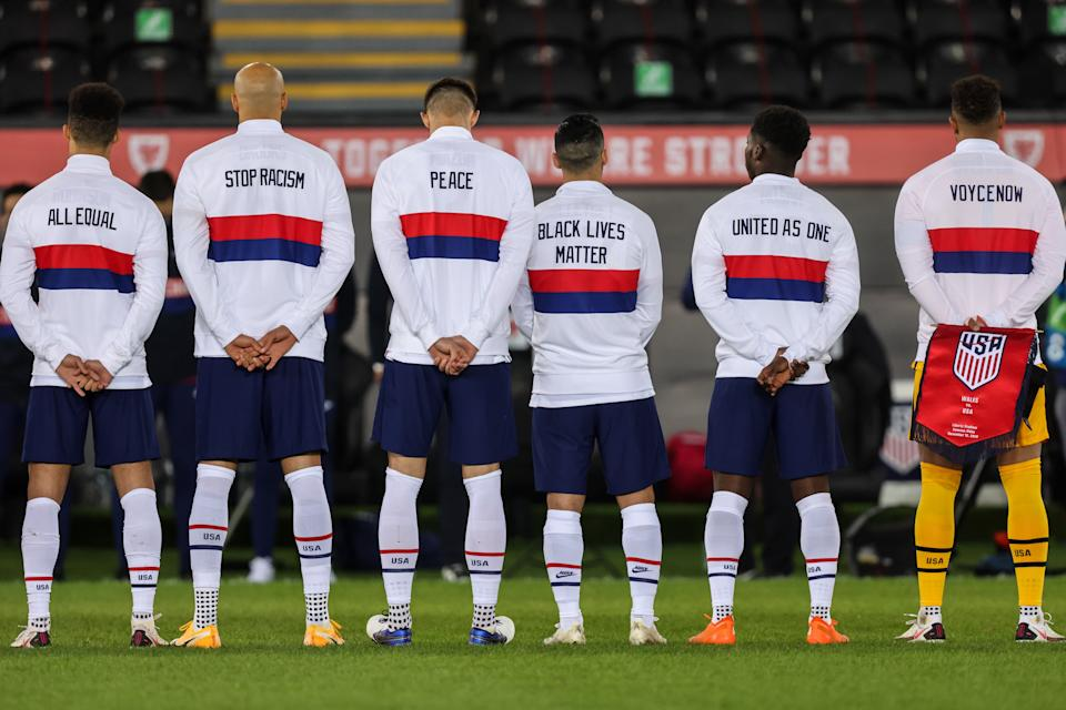 SWANSEA, WALES - NOVEMBER 12:  Players of United States of America line up for the national anthems with messages on the back of their jackets during the international friendly match between Wales and the USA at Liberty Stadium on November 12, 2020 in Swansea, Wales. Sporting stadiums around the UK remain under strict restrictions due to the Coronavirus Pandemic as Government social distancing laws prohibit fans inside venues resulting in games being played behind closed doors. (Photo by Matthew Ashton - AMA/Getty Images)