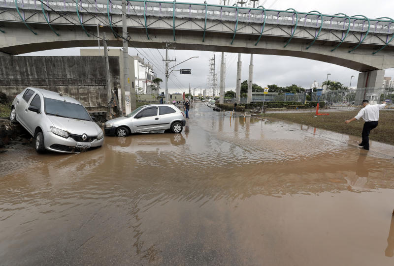 Vehicles are stuck in a flooded street in Sao Paulo, Brazil, Monday, March 11, 2019. According to The Sao Paulo state fire department, heavy rains caused the deaths of at least 11 people in and around Brazil's largest city, including a 1-year-old baby. (AP Photo/Andre Penner)