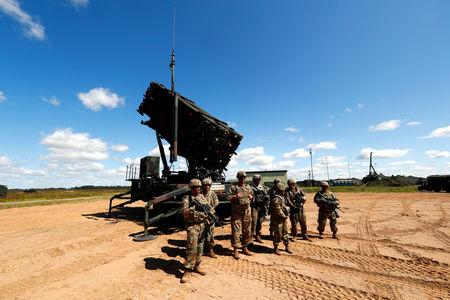 U.S. soldiers stand next to the long-range air dfence system Patriot during Toburq Legacy 2017 air defence exercise in the military airfield near Siauliai