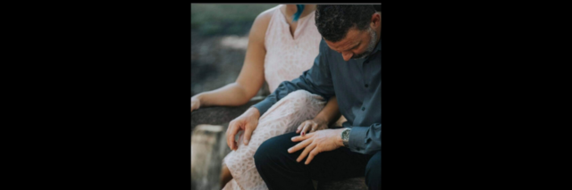 A man and a woman sit on an outside benching touching each other.