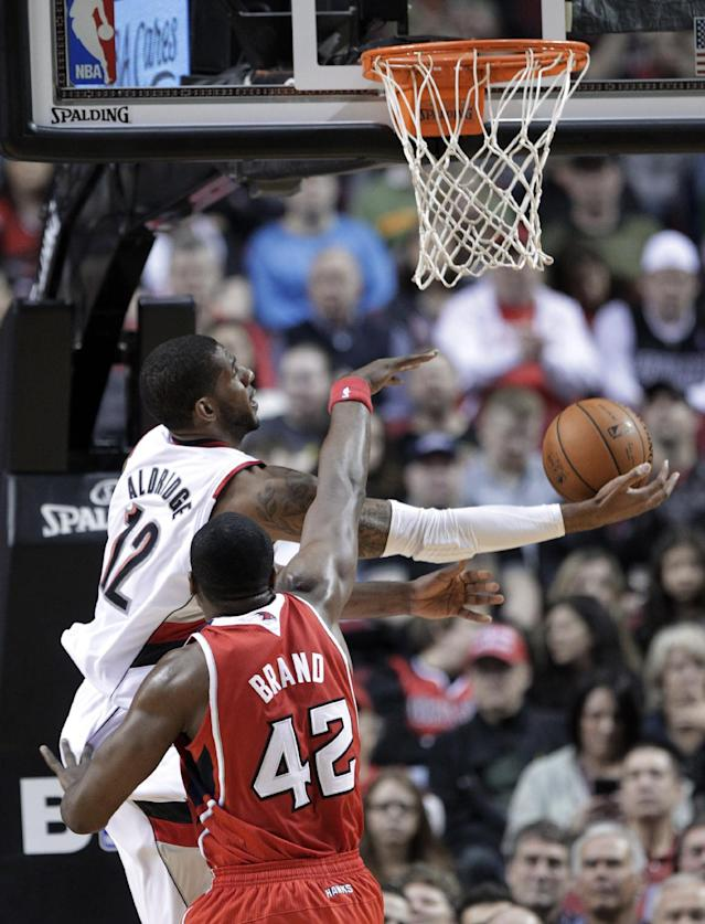 Portland Trail Blazers forward LaMarcus Aldridge, left, goes for a reverse layup against Atlanta Hawks center Elton Brand during the first half of an NBA basketball game in Portland, Ore., Wednesday, March 5, 2014. (AP Photo/Don Ryan)