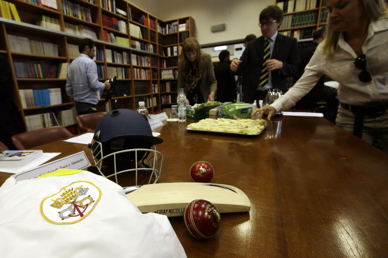 """A Vatican jersey and cricket equipment is displayed on a table as journalists enjoy cucumber sandwiches at the end of a press conference at the Vatican, Tuesday, Oct. 22, 2013. The Vatican has officially launched its cricket club, an initiative aimed at forging ties with teams of other faiths. Pope Francis marked the occasion by having tea and cucumber sandwiches served for a sport long associated with manicured grounds and English nobility. But the soccer-mad """"slum pope"""" still prefers that lower-brow sport. He and the Vatican have long championed sports as good for the mind, body and soul. The cricket club is the latest initiative of the Vatican's culture ministry to use sports to engage in dialogue with the contemporary world. (AP Photo/Gregorio Borgia)"""