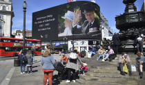 Images of Britain's Prince Philip are displayed on a giant screen at Piccadilly Circus, London Saturday, April 17, 2021. Prince Philip, husband of Queen Elizabeth II, died Friday April 9 aged 99. His funeral service is taking place at St. George's Chapel inside Windsor Castle Saturday. (AP Photo/Rui Vieira)
