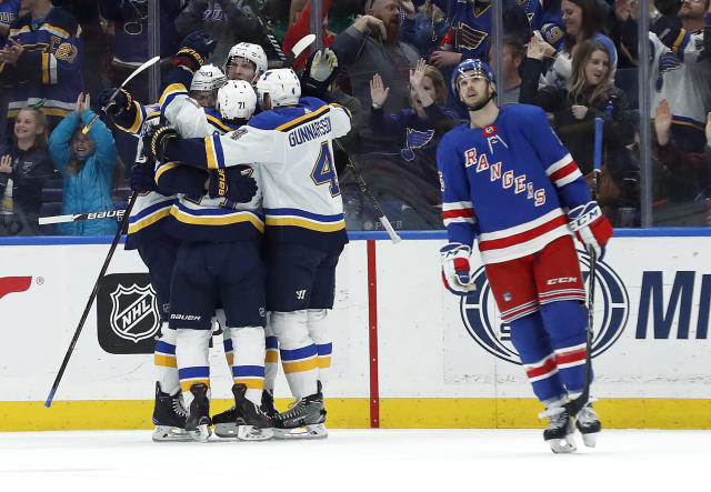 Members of the St. Louis Blues surround teammate Alex Pietrangelo after his goal as New York Rangers' Ryan Sproul, right, skates past during the first period of an NHL hockey game Saturday, March 17, 2018, in St. Louis. (AP Photo/Jeff Roberson)