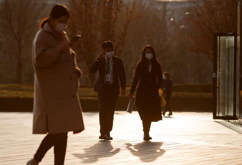 Office workers face masks outside an office complex in Beijing as the country is hit by an outbreak of the novel coronavirus