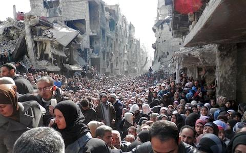 Residents wait in line to receive food aid distributed in the Yarmouk refugee camp on January 31, 2014 in Damascus, Syria. - Credit: UNRWA