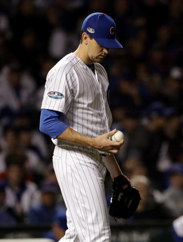 Chicago Cubs relief pitcher Kyle Hendricks looks down as he checks the ball after Colorado Rockies' Gerardo Parra hit a single during the 13th inning of the National League wild-card playoff baseball game Tuesday, Oct. 2, 2018, in Chicago. (AP Photo/Nam Y. Huh)