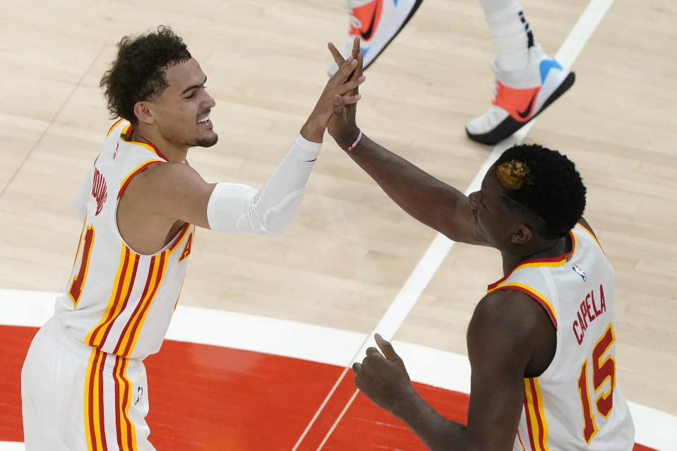 Atlanta Hawks guard Trae Young (11) and Atlanta Hawks center Clint Capela (15) celebrate during the second half of an NBA basketball game against the New Orleans Pelican Tuesday, April 6, 2021, in Atlanta. (AP Photo/John Bazemore)