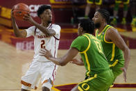 Oregon forward Chandler Lawson (13) and guard LJ Figueroa, right, defend against Southern California guard Tahj Eaddy (2) during the second half of an NCAA college basketball game Monday, Feb. 22, 2021, in Los Angeles. (AP Photo/Ashley Landis)