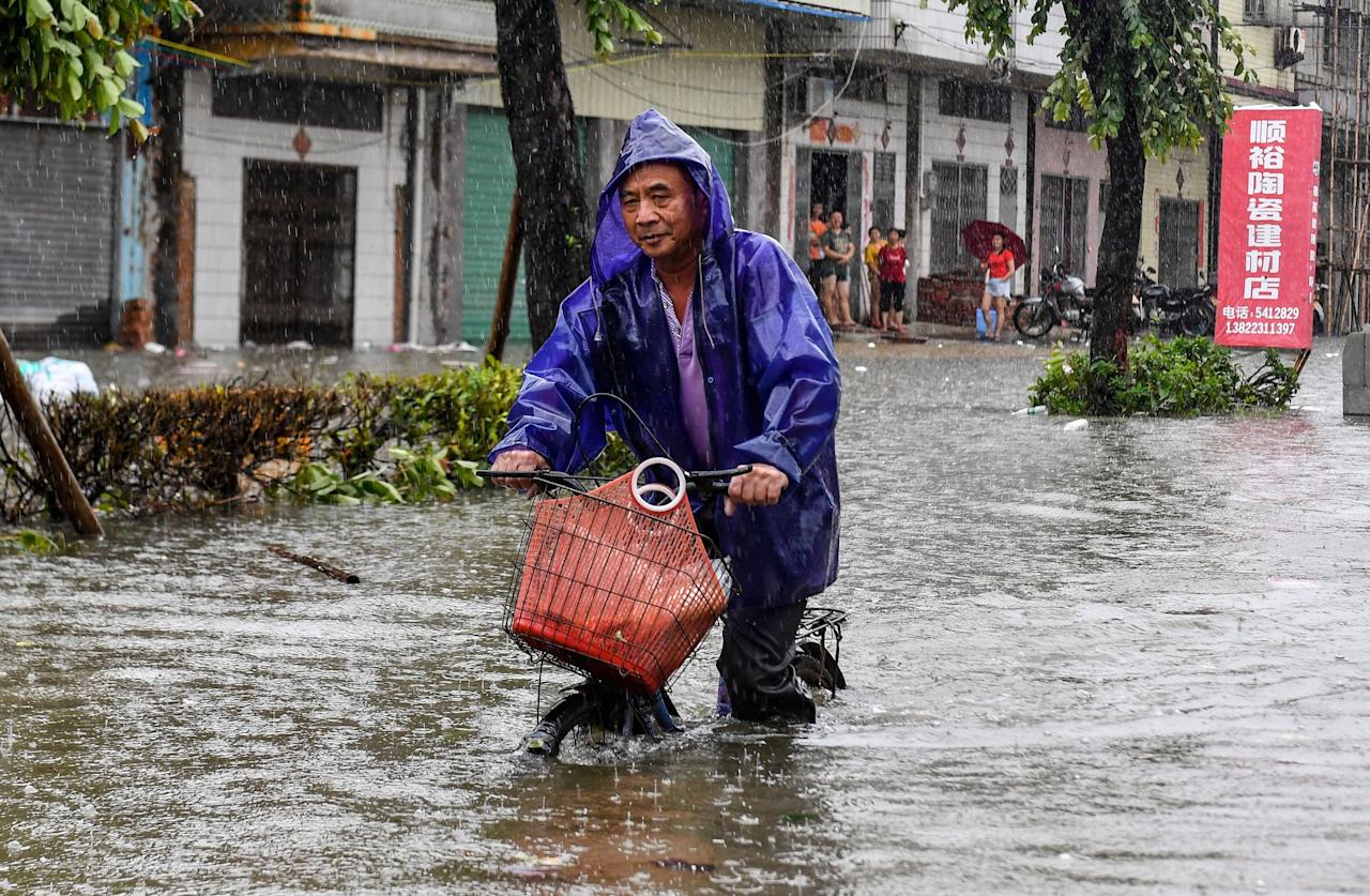<p>A cyclist rides on a flooded road after heavy rainstorms caused by Typhoon Mangkhut in China. (Rex) </p>