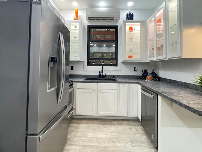 the kitchen with a fridge, sink, countertop, storage