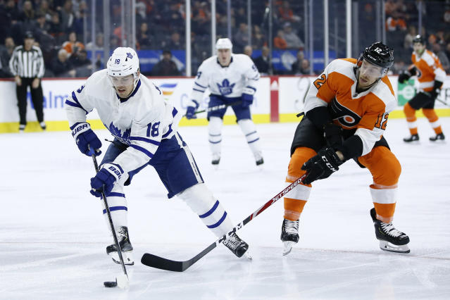 Toronto Maple Leafs' Andreas Johnsson (18) tries to keep the puck away from Philadelphia Flyers' Michael Raffl (12) during the first period of an NHL hockey game, Tuesday, Dec. 3, 2019, in Philadelphia. (AP Photo/Matt Slocum)