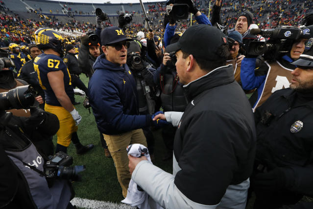 Michigan head coach Jim Harbaugh, left, shakes hands with Ohio State head coach Ryan Day after an NCAA college football game in Ann Arbor, Mich., Saturday, Nov. 30, 2019. Ohio State won 56-27. (AP Photo/Paul Sancya)