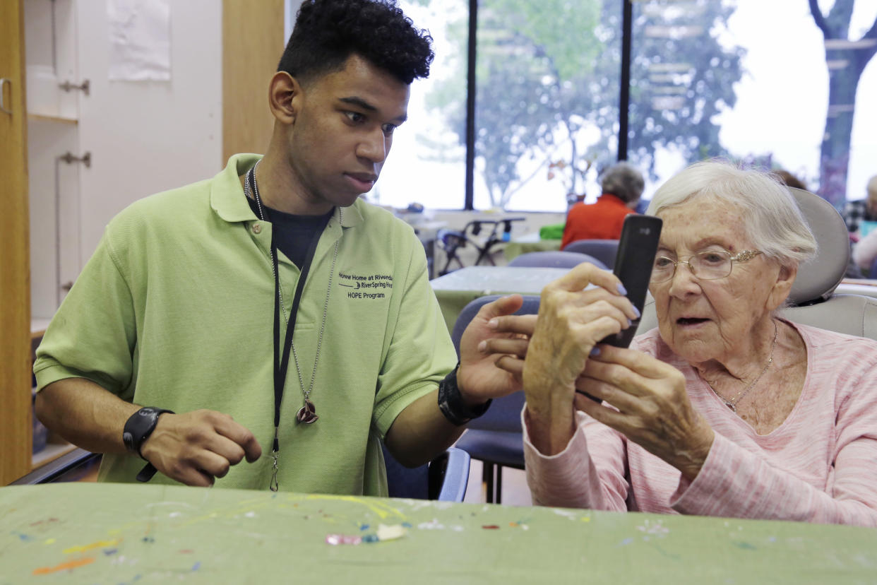 Kevin Perez, 19, in the HOPE program at the Hebrew Home at Riverdale, in New York, assists resident Belle Bishop, age 93, with her mobile phone in the art studio Thursday, May 25, 2017. (AP Photo/Richard Drew)
