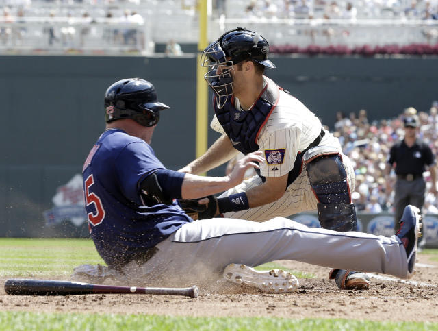 Cleveland Indians' Jason Giambi, left, slides by Minnesota Twins catcher Joe Mauer to score on a two-run single by Mike Aviles in the fourth inning of a baseball game, Wednesday, Aug. 14, 2013 in Minneapolis. (AP Photo/Jim Mone)