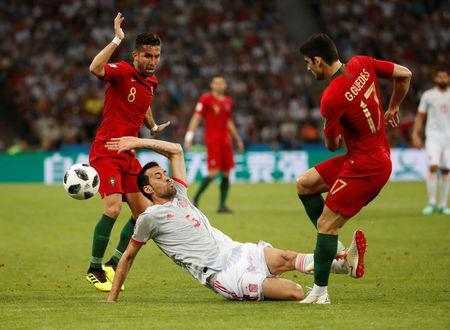 Spain's Sergio Busquets fouls Portugal's Goncalo Guedes prompting referee Gianluca Rocchi to award Busquets a yellow card. REUTERS/Francois Lenoir