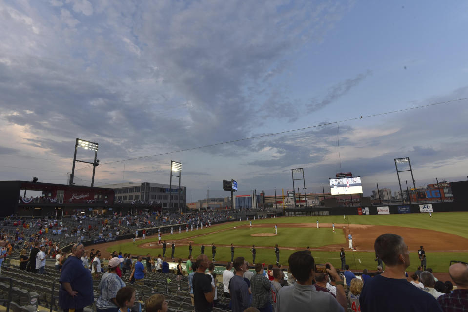 FILE - Players stand during the national anthem before the Rosemont Dogs played their baseball home-opener against the Milwaukee Milkmen at Impact Field in Rosemont, Ill., in this Tuesday, July 7, 2020, file photo. Minor league teams across the country are set to open their seasons Tuesday, May 4, 2021, returning baseball to communities denied the old national pastime during the coronavirus pandemic. (John Starks/Daily Herald, via AP, File)