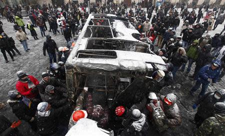 Demonstrators pull a burnt vehicle during a rally held by pro-European integration protesters in Kiev January 21, 2014. REUTERS/Vasily Fedosenko