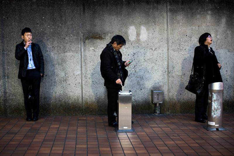 Men smoke cigarettes at a designated outdoor smoking area in the Naka-Meguro neighborhood of Tokyo. A local company is offering nonsmoking employees extra paid time off.