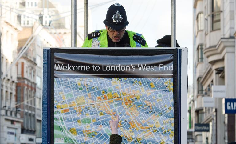 A police officer gives advice to a shopper in Oxford Street in central London on December 16, 2012