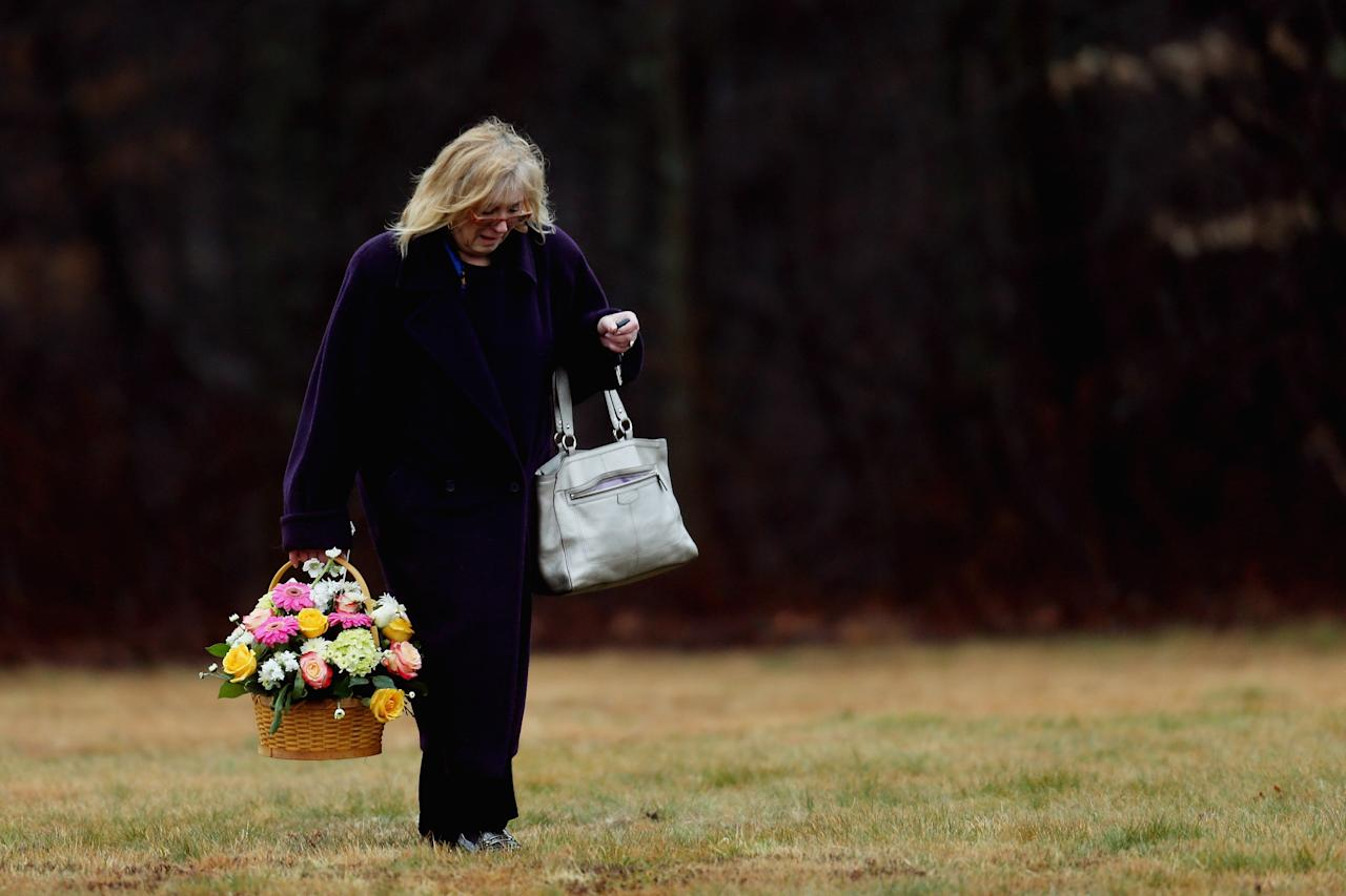 MONROE, CT - DECEMBER 17:  A woman carries a basket of flowers at the funeral services for six year-old Noah Pozner, who was  killed in the shooting massacre in Newtown, CT, at B'nai Israel Cemetery on December 17, 2012 in Monroe, Connecticut. Today is the first day of funerals for some of the twenty children and seven adults who were killed by 20-year-old Adam Lanza on December 14, 2012.  (Photo by Spencer Platt/Getty Images)