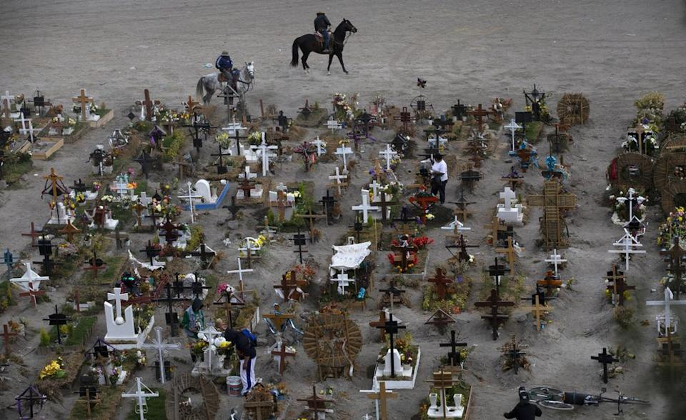 workers ride their horses in the Valle de Chalco municipal cemetery, mostly reserved for those who have died from the coronavirus, on the outskirts of Mexico City