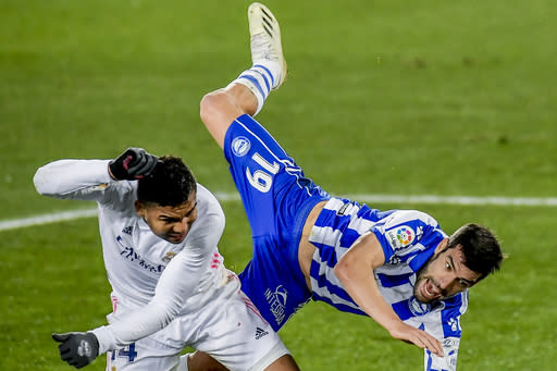 Real Madrid's Casemiro, left, vies for the ball with Alaves' Manu Garcia during the Spanish La Liga soccer match between Alaves and Real Madrid at Mendizorroza stadium in Vitoria, Spain, Saturday, Jan. 23, 2021. (AP Photo/Alvaro Barrientos)