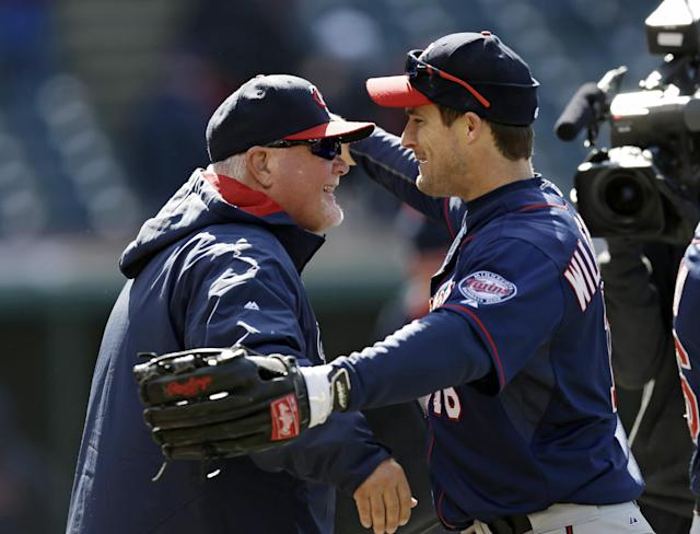 Minnesota Twins' Josh Willingham, right, congratulates Minnesota Twins manager Ron Gardenhire after the Twins defeated the Cleveland Indians 7-3 in a baseball game, Saturday, April 5, 2014, in Cleveland. The Twins win Saturday gave Gardenhire his 1,000th career victory. (AP Photo/Tony Dejak)