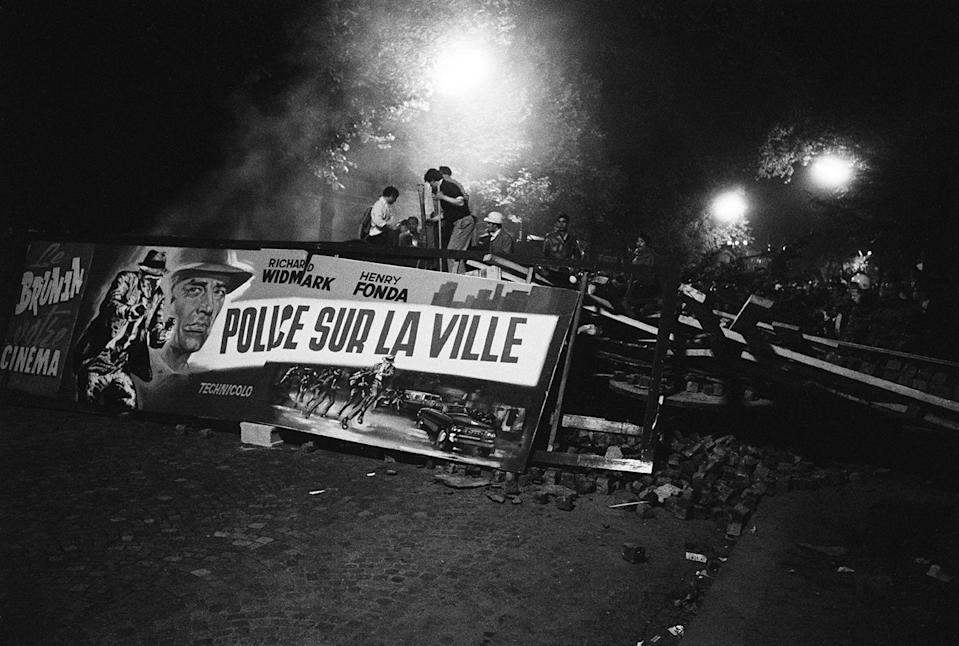 """<p>Demonstrating students found a ready-made propaganda banner when they tore down a movie marquee advertising a police film, """"Police sur la Ville,"""" (""""Madigan"""") co-starring Richard Widmark and Henry Fonda, on the Boulevard Saint-Michel in Paris, May 10-11, 1968. (Photo: Gökşin Sipahioğlu/SIPA) </p>"""