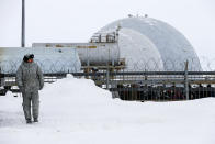 A soldier walks at a radar facility on the Alexandra Land island near Nagurskoye, Russia, Monday, May 17, 2021. Once a desolate home mostly to polar bears, Russia's northernmost military outpost is bristling with missiles and radar and its extended runway can handle all types of aircraft, including nuclear-capable strategic bombers, projecting Moscow's power and influence across the Arctic amid intensifying international competition for the region's vast resources. (AP Photo/Alexander Zemlianichenko)