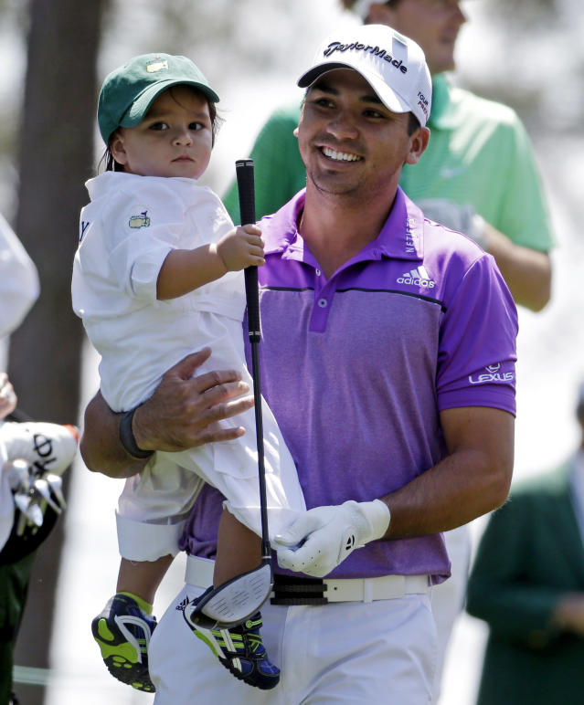 Jason Day, of Australia, carries his son Dash during the par three competition at the Masters golf tournament Wednesday, April 9, 2014, in Augusta, Ga. (AP Photo/Darron Cummings)
