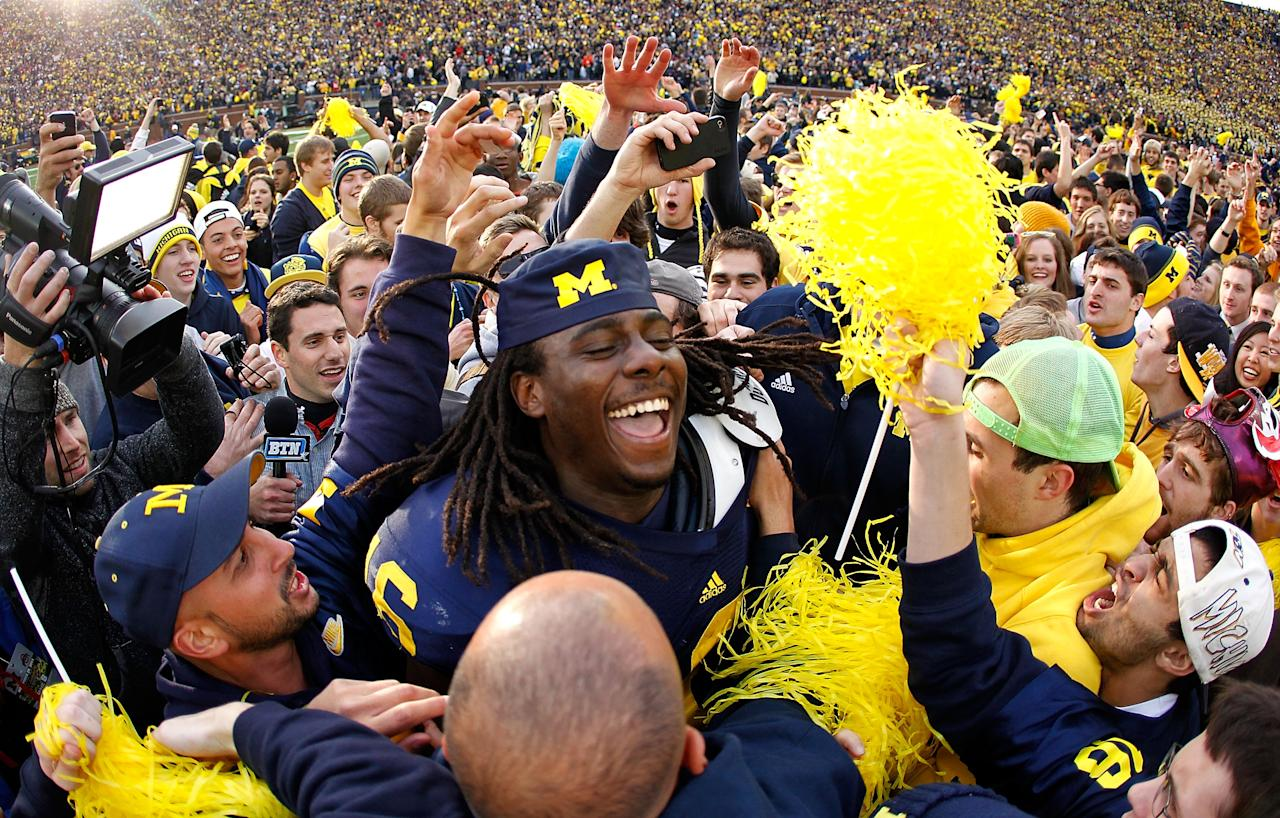 ANN ARBOR, MI - NOVEMBER 26:  Denard Robinson #16 of the Michigan Wolverines celebrates with students after beating Ohio State 40-34 at Michigan Stadium on November 26, 2011 in Ann Arbor, Michigan. (Photo by Gregory Shamus/Getty Images)