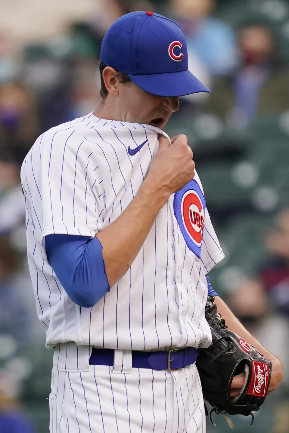 Chicago Cubs starting pitcher Kyle Hendricks wipes his face after Atlanta Braves' Ehire Adrianza hit a solo home run during the first inning of a baseball game in Chicago, Sunday, April 18, 2021. (AP Photo/Nam Y. Huh)
