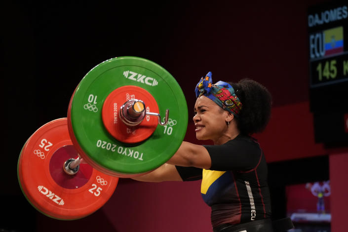 Neisi Patricia Dajomes Barrera of Ecuador lowers the barbell after her final lift, in the women's 76kg weightlifting event, at the 2020 Summer Olympics, Sunday, Aug. 1, 2021, in Tokyo, Japan. (AP Photo/Luca Bruno)