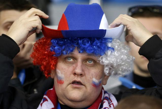 A Russian team supporter adjusts his hat during the women's ice hockey game against Germany at the 2014 Sochi Winter Olympics, February 9, 2014. REUTERS/Mark Blinch (RUSSIA - Tags: SPORT OLYMPICS ICE HOCKEY TPX IMAGES OF THE DAY)
