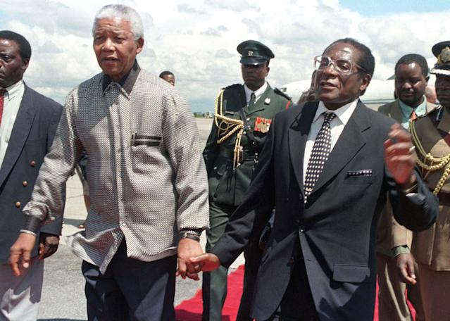 <p>Mugabe holds hands with his South African counterpart, Nelson Mandela, greeting him on his arrival in the country in 1998. Mandela was in Zimbabwe to address the World Council of Churches. (Photo: Howard Burditt/Reuters) </p>