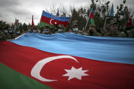 Azerbaijani soldiers hold a huge national flag as they celebrate the transfer of the Lachin region to Azerbaijan's control, as part of a peace deal that required Armenian forces to cede the Azerbaijani territories they held outside Nagorno-Karabakh, in Aghjabadi, Azerbaijan, Tuesday, Dec. 1, 2020. Azerbaijan has completed the return of territory ceded by Armenia under a Russia-brokered peace deal that ended six weeks of fierce fighting over Nagorno-Karabakh. Azerbaijani President Ilham Aliyev hailed the restoration of control over the Lachin region and other territories as a historic achievement. (AP Photo/Emrah Gurel