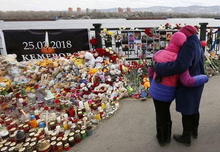 FILE PHOTO: People visit a makeshift memorial on the day of national mourning for the victims of a shopping mall fire in Kemerovo on an embankment of the Yenisei River in the Siberian city of Krasnoyarsk, Russia March 28, 2018. REUTERS/Ilya Naymushin/File Photo