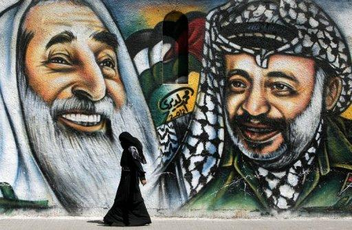A woman walks past a mural of Yasser Arafat (right) and late Hamas spiritual leader Sheikh Ahmed Yassin