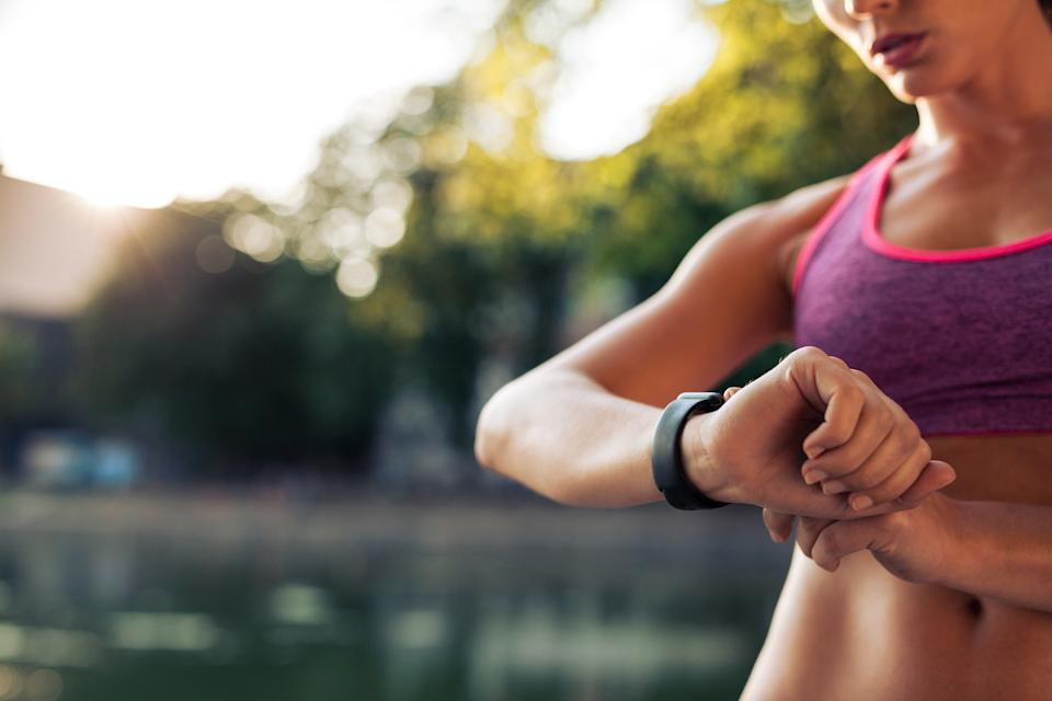 Woman setting up the fitness smart watch for running. Sportswoman checking watch device.