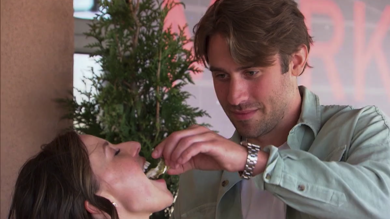 """Greg pours an oyster he just """"shucked"""" into Katie's open mouth"""