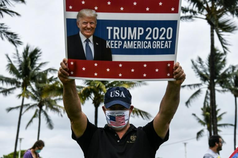 A Trump supporter holds a poster of the president in Miami in May 2020