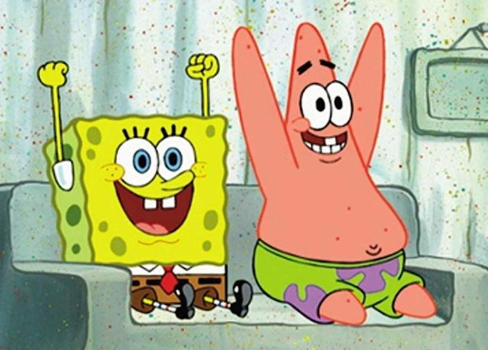 SpongeBob Squarepants and Patrick raise their hands above their head while watching TV from a couch made of sand
