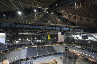 The interior beams of the historic peaked roof of the Climate Pledge Arena rise above the United States and team flags during a media tour of the facility, Monday, July 12, 2021, in Seattle. The arena will be the home of the NHL hockey team Seattle Kraken and the WNBA Seattle Storm basketball team as well as hosting concerts and other performing arts events. (AP Photo/Ted S. Warren)