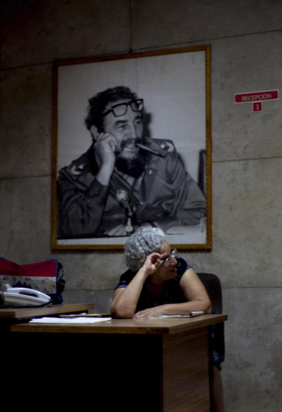 A woman sits in a community center where a photograph of Fidel Castro hangs on the wall in Old Havana, Cuba, Sunday, Aug. 12, 2012. Castro turns 86 on Monday. The last time Castro attended a public event was during the Communist Party congress on April 19, 2011, but he has met privately with others, like Pope Benedict XVI in March this year. (AP Photo/Ramon Espinosa)